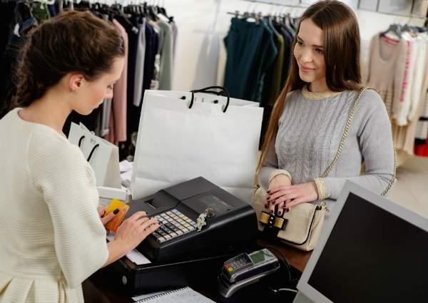 Glueckliche Frau bezahlt mit Kreditkarte in einem Bekleidungsgeschaeft