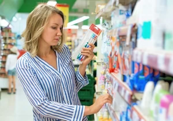 Junge Frau waehlt eine Zahnbuerste im Supermarkt