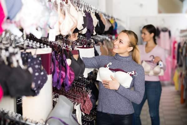 Frau waehlt BHs im Dessous-Shop aus