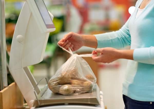 Frau wiegt Kartoffeln im Lebensmittelgeschaeft
